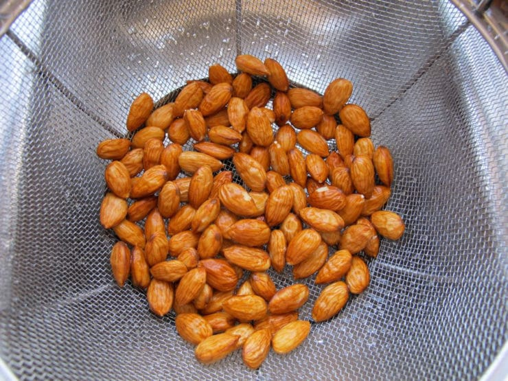 Wet almonds draining in mesh strainer colander, close up - almond skins slightly shriveled.