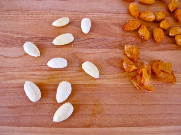 Nine skinned almonds with loose skins beside them, pile of un-skinned almonds on the side.