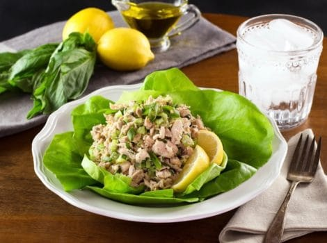 Healthy tuna salad on bed of green butter lettuce with lemon slices, on white plate with fork and cloth napkin, glass of ice water, lemons basil and olive oil in background.