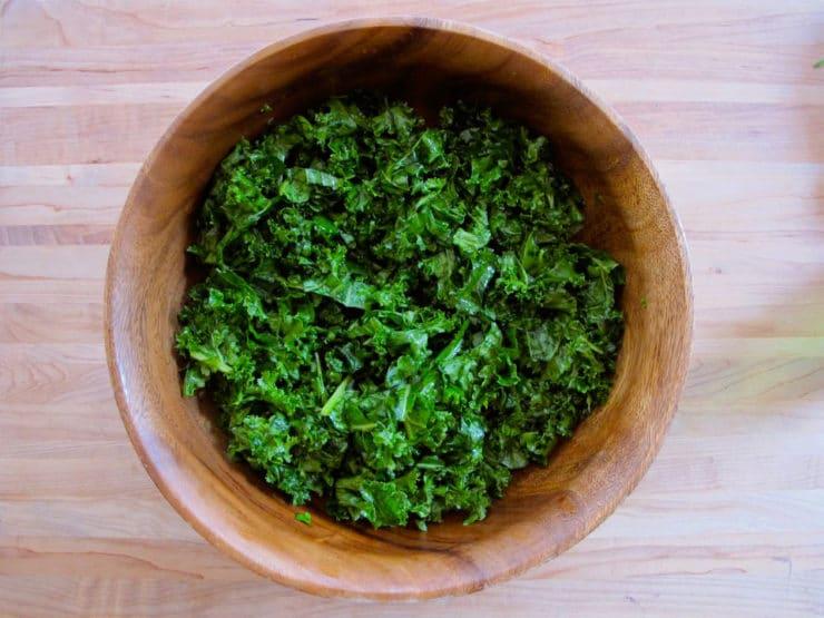 Massaging kale in a salad bowl.