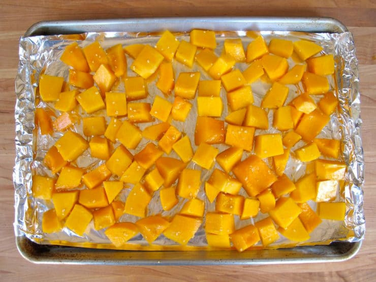 Butternut squash cubes on a foil lined baking sheet.