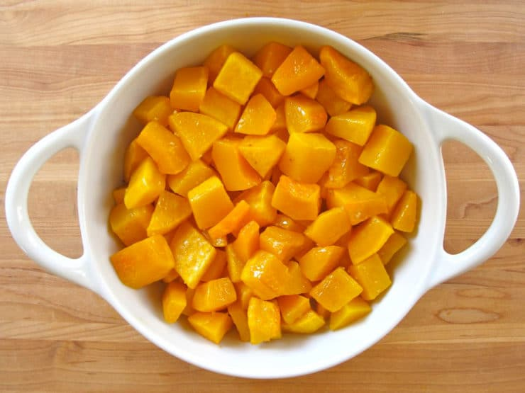 Roasted butternut squash cubes in a gratin dish.