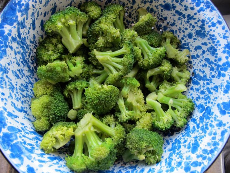 Steamed broccoli florets in a colander.