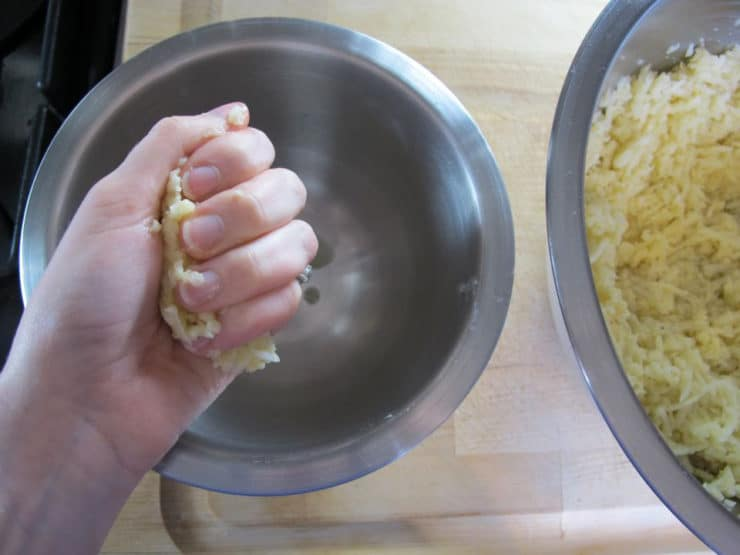 Squeezing shredded potatoes.