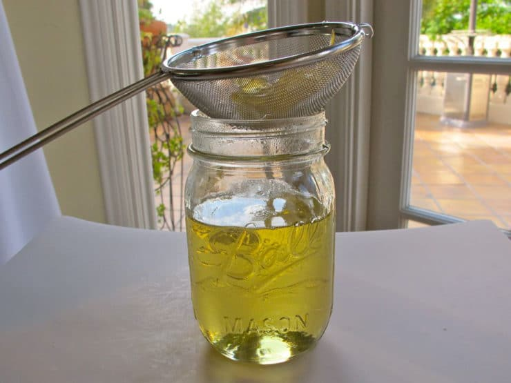 Straining lemon simple syrup into a jar.