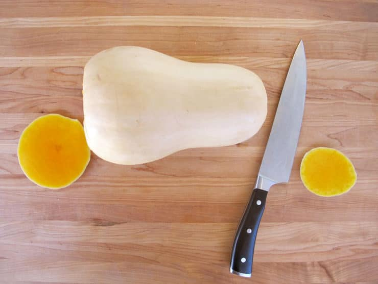 Slice the ends off a butternut squash.