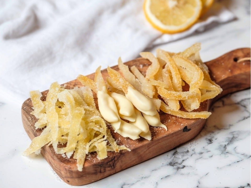 Horizontal shot - wide shot of candied lemon peels on a small wood cutting board on marble counter. Large peels, small peels, peels dipped in white chocolate. Lemon half and white linen towel in background.