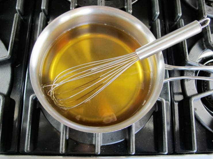 Dissolving sugar in apple cider in a saucepan.