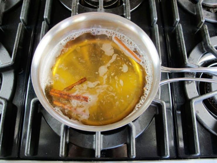 Simmering spices in apple cider in a saucepan.