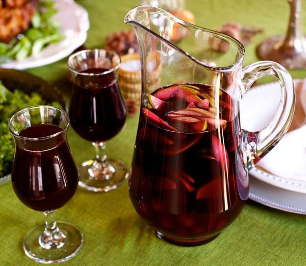A glass pitcher filled with red sangria and thinly sliced green apples next to two glasses of sangria atop a green tablecloth.