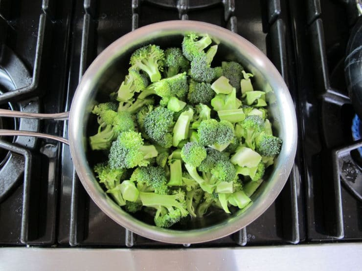 Raw broccoli in a pot of water.
