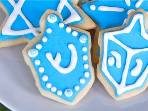 Close up on dreidel-shaped cookie decorated with royal icing and blue candy beads.