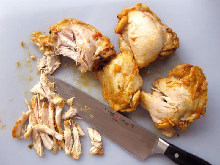 Slicing chicken thighs.