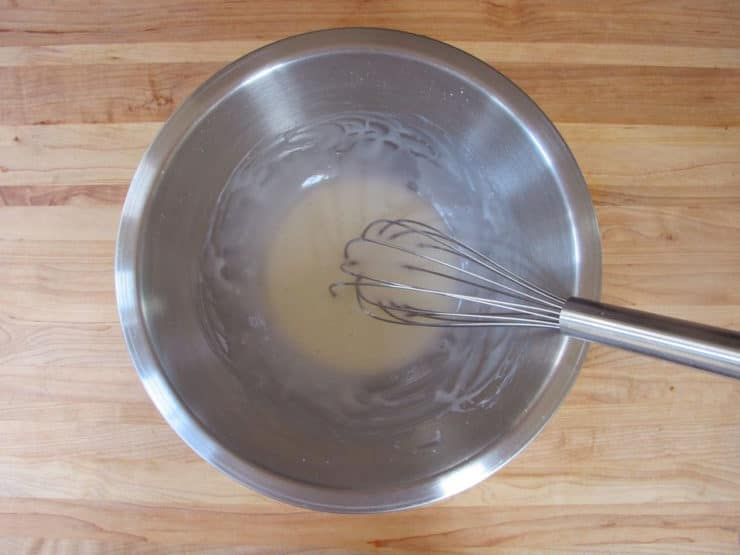 Whisking glaze in a small bowl.