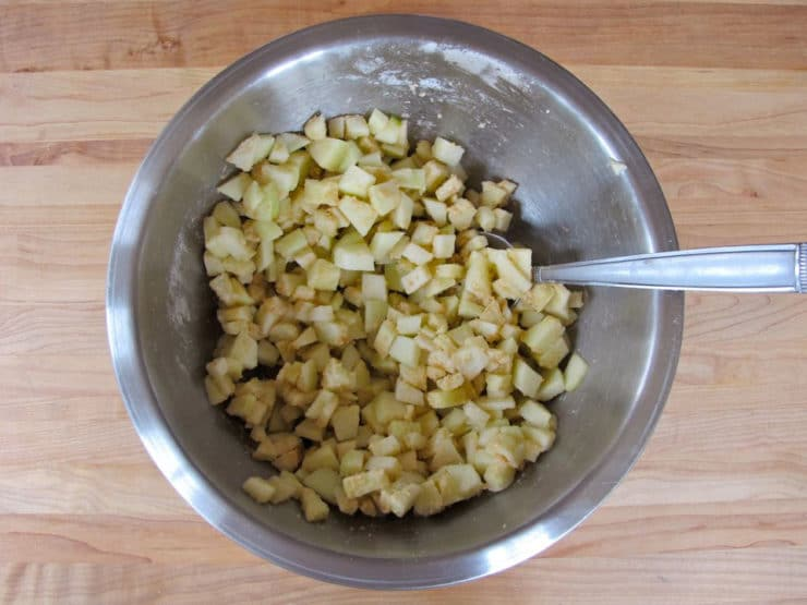 Tossing diced apples in cinnamon sugar.