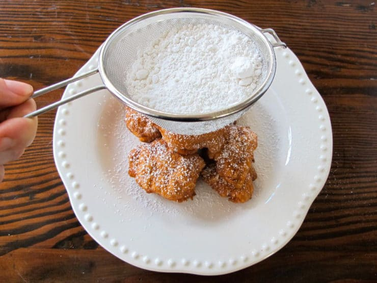 Dusting fritters with powdered sugar.