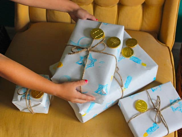 Young hands holding gifts wrapped with homemade holiday gift wrap.