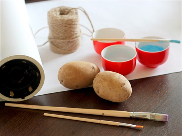 Supplies for wrapping paper - potatoes, paintbrushes, twine, paper.