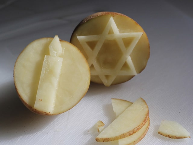Potato stamps craved with star of David and candle.