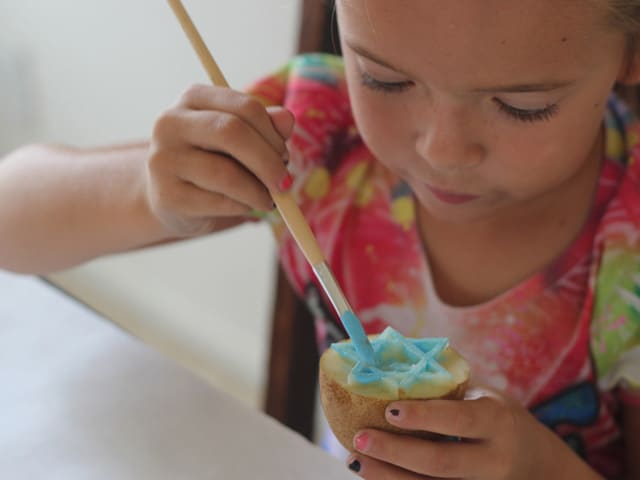 Young girl painting potato stamp with blue paint.