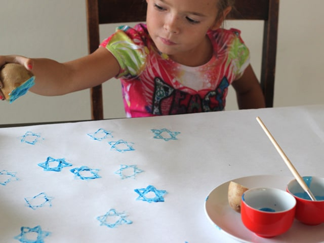 Young girl stamping Hanukkah wrapping paper with star of David potato stamp.