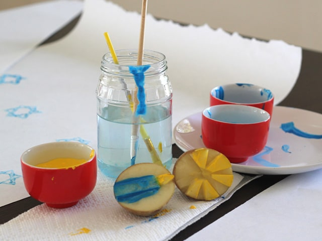 Potato stamps painted with blue and yellow paint, paintbrushes in jar of water, red pots with paint.