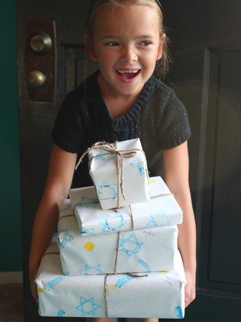 Girl smiling holding gifts wrapped in homemade Hanukkah gift wrap.