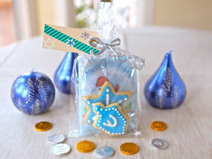 Fully assembled Homemade Cookies and Hot Cocoa Gift Bag on table surrounded by blue holiday candles and gelt.