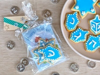 Assembled hot cocoa and cookies holiday gift bag with plate of cookies and Hanukkah gelt.