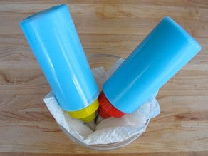 Two icing bottles tip down in bowl lined with wet paper towel.