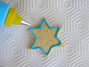 Decorating star of David sugar cookie. Outline with blue icing.