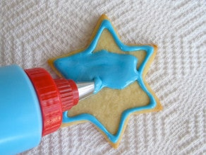 Decorating star of David sugar cookie. Flooding outline with blue icing.