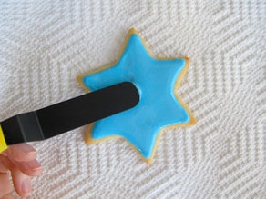 Decorating star of David sugar cookie. Smoothing surface of blue icing with small spatula.