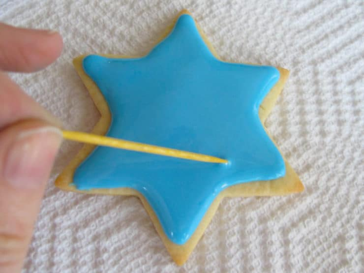 Decorating star of David sugar cookie. Popping bubbles in blue icing with toothpick.
