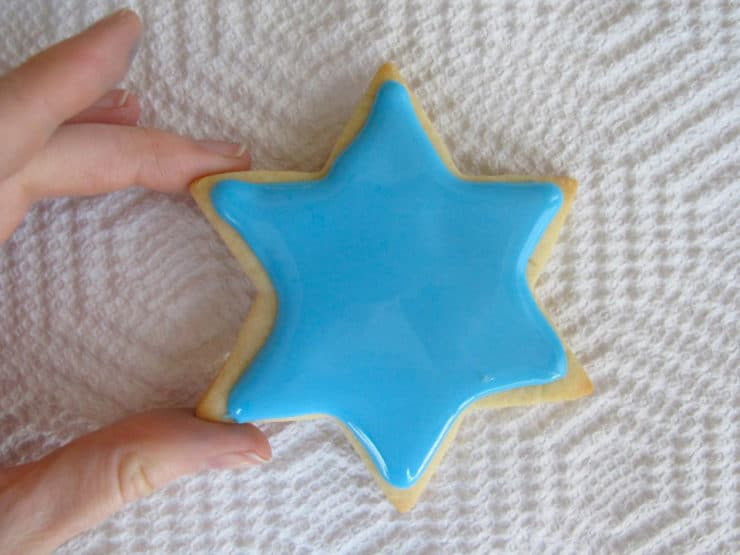 Decorating star of David sugar cookie. Fingers holding cookie edges.