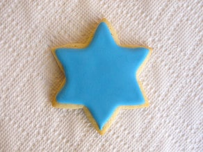 Star of David sugar cookie with bed of blue frosting, complete.