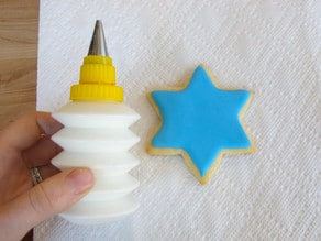 Hand holding small bottle of white royal icing next to blue iced star of David cookie.