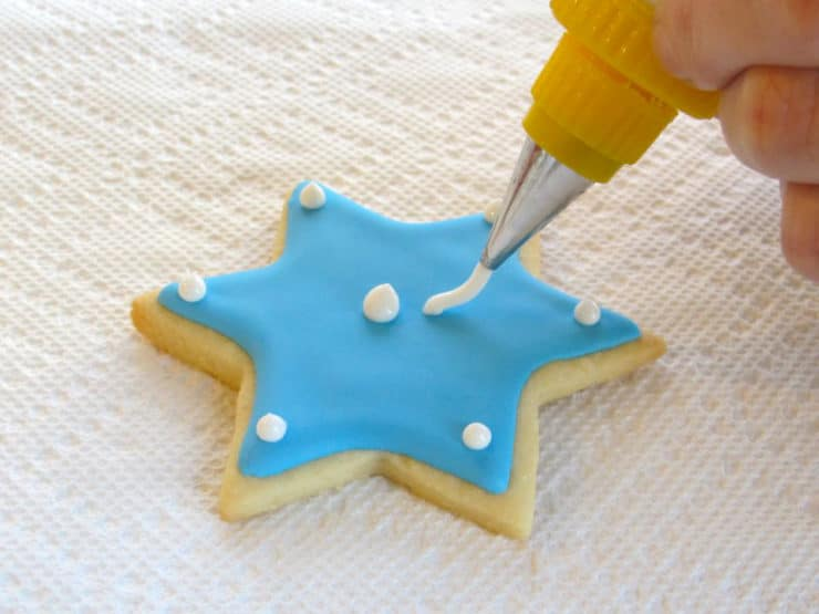 White royal icing dot details being added to blue Jewish holiday sugar cookie.
