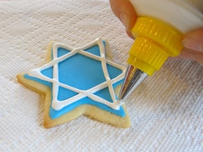 White royal icing linear details being added to blue Jewish holiday sugar cookie.