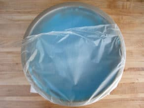 Bowl of icing covered with plastic wrap.