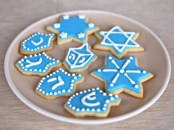 Front View - Plate of Hanukkah Holiday Sugar Cookies Decorated with Royal Icing on Beige Plate on Beige Tablecloth