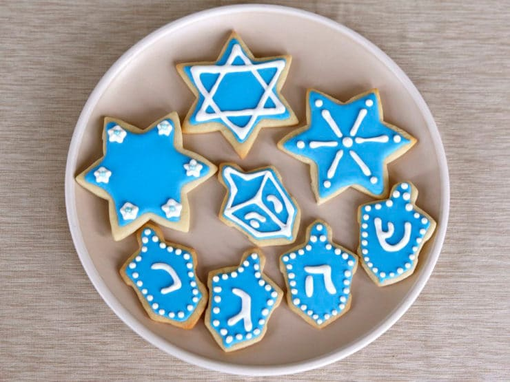 overhead view plate of hanukkah holiday sugar cookies decorated with royal icing on beige plate