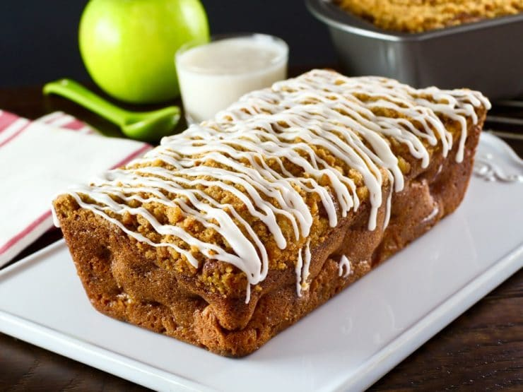 Greek Yogurt Apple Streusel Cake unsliced on white plate with cloth napkins, dish of yogurt, spook and green apple in background.