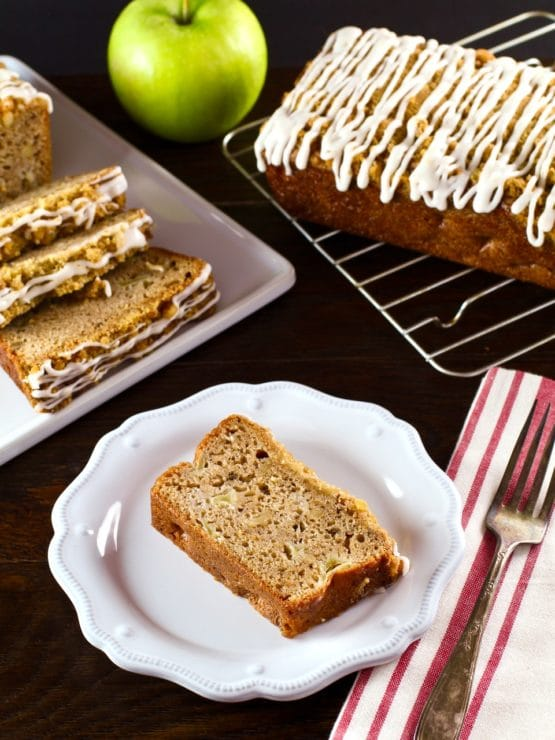 Vertical shot of slice of Greek Yogurt Apple Streusel Cake on white plate with cloth napkin and fork, sliced cake and whole loaf cake on baking rack with green apple in background.