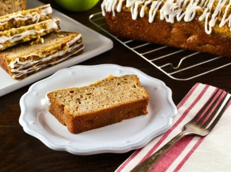 Horizontal shot of slice of Greek Yogurt Apple Streusel Cake on white plate with cloth napkin and fork, sliced cake and whole loaf cake on baking rack with green apple in background.