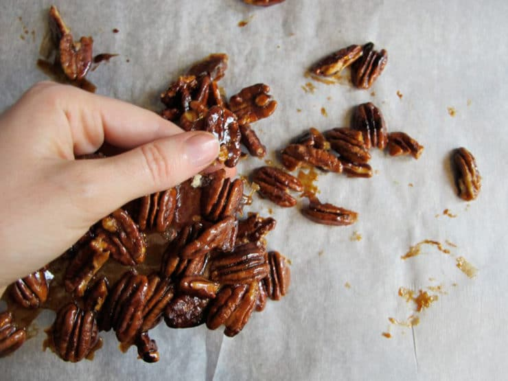 Breaking candied pecans into pieces.