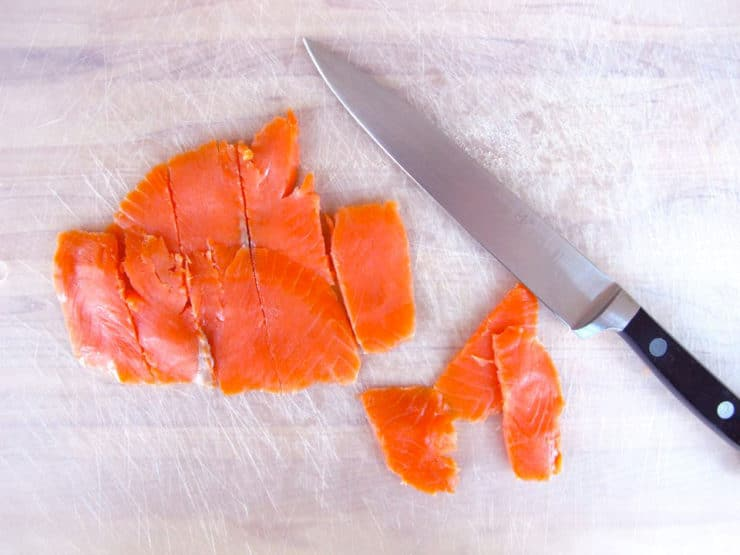 Slicing smoked salmon on a cutting board.