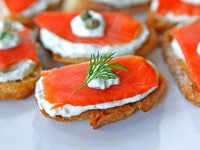 Salmon crostini topped with dill.