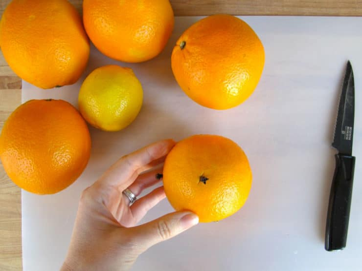 Sticking cloves into oranges.