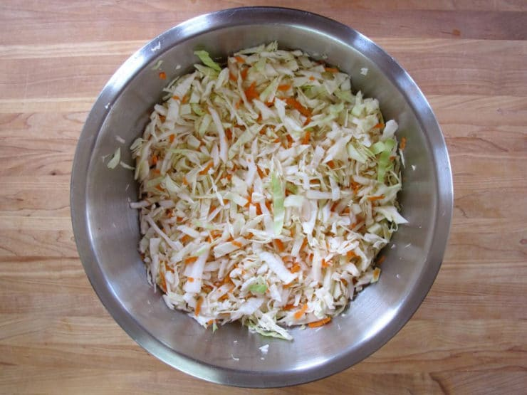 Shredded cabbage and carrots in a mixing bowl.